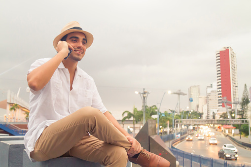 Latin fit male using his cellphone / smartphone with 5G Technology at Guayaquil, Ecuador
