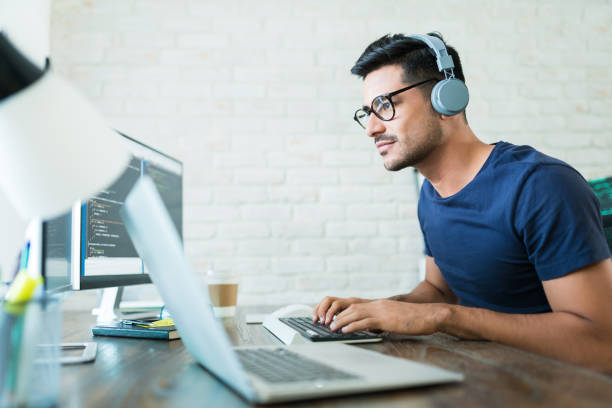Latin Freelance Coding Expert Using Computer At Desk stock photo