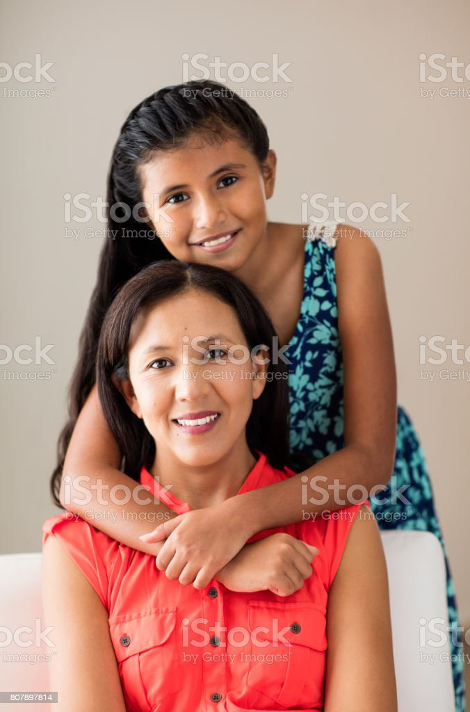 Latin girl embracing mother from behind and smiling at camera stock photo