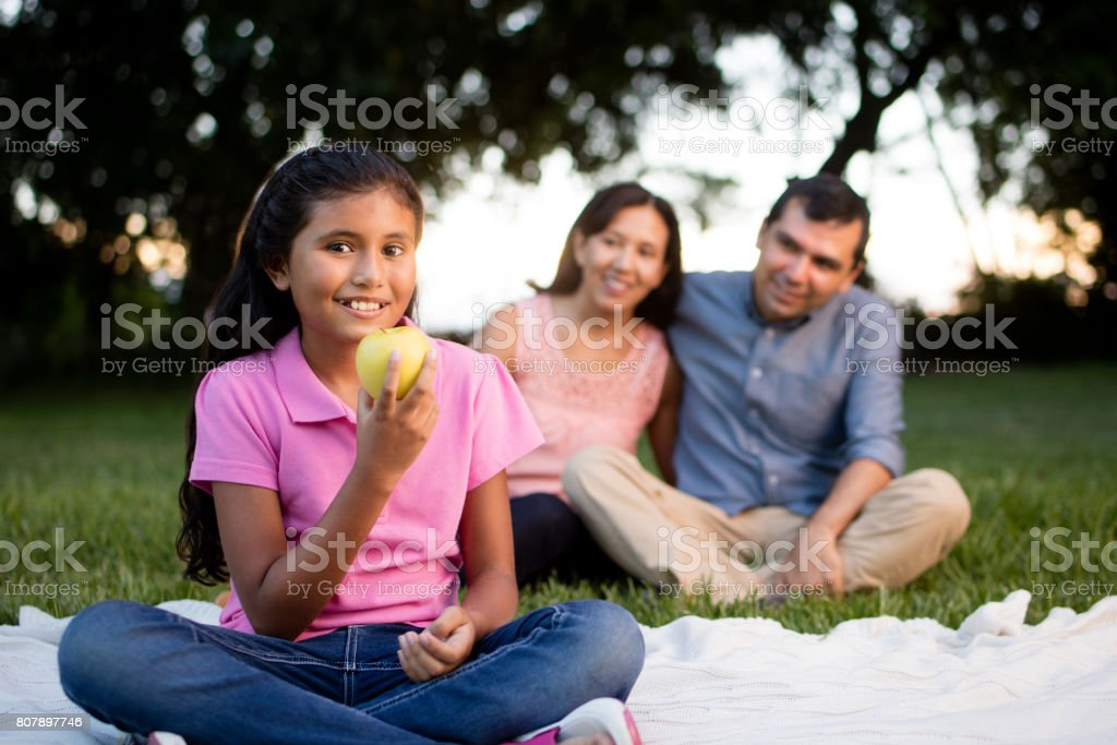 Latin girl holding apple and smiling at camera stock photo