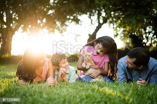 811227514 istock photo Latin girl holding cat and sitting with her family 811220692