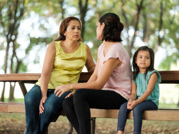 Latin girl sitting next to mother and grandmother outside stock photo