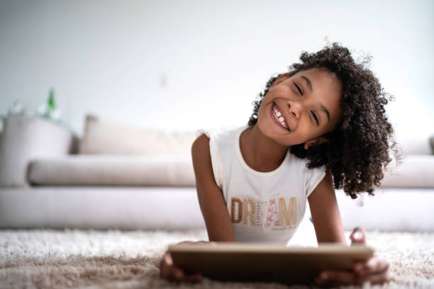 """Latin girl using digital tablet at home - portrait In a world where children are """"growing up digital,"""" it's important to help them learn healthy concepts of digital use and citizenship 8 9 years stock pictures, royalty-free photos & images"""