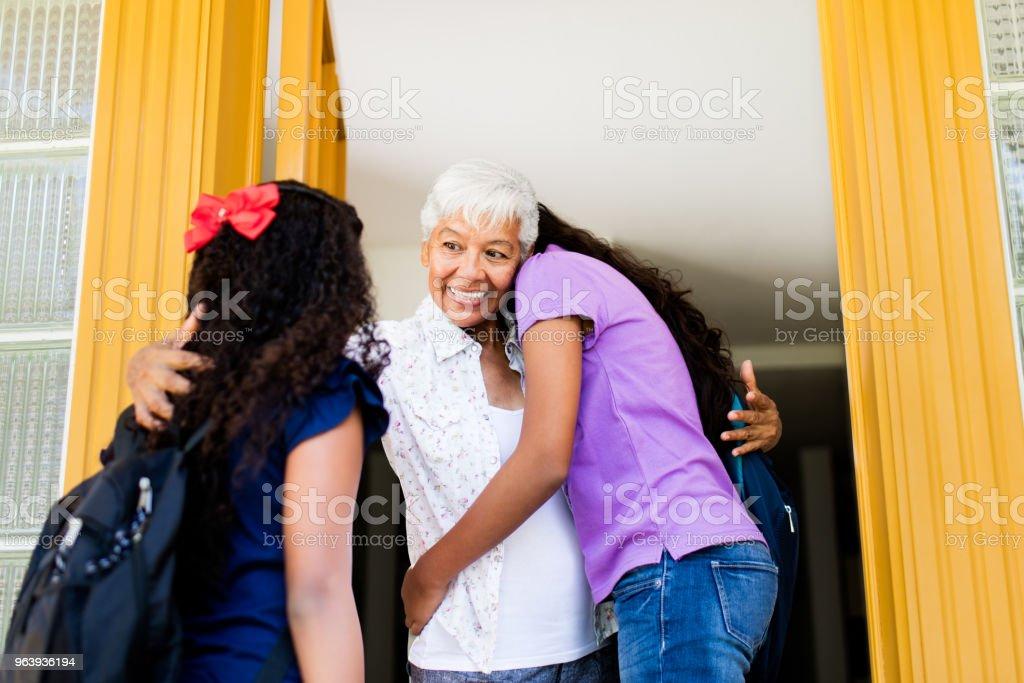 Latin grandma welcoming and hugging her granddaughters - Royalty-free 12-13 Years Stock Photo