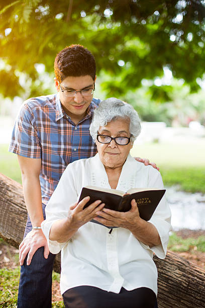 Latin grandmother and grandson reading Bible – Foto