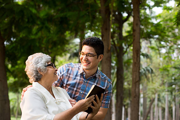 Latin grandmother reading Bible and smiling at grandson – Foto