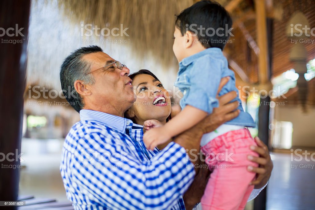 Latin grandparents holding grandson and smiling - foto de stock