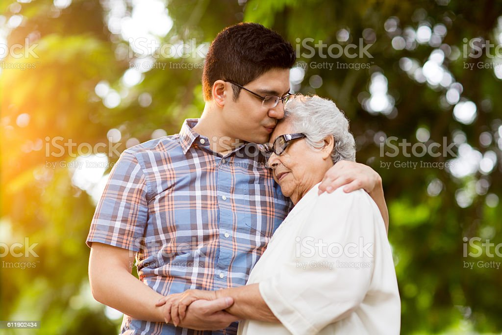 Latin grandson and grandmother embracing with eyes closed - foto de stock
