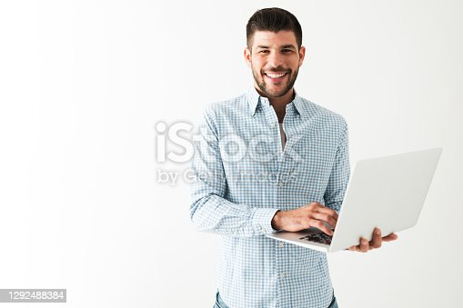 istock Latin guy is smiling while typing on a laptpop 1292488384