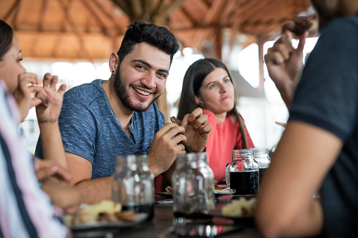 Latin Hombre looks at the camera and smiles, is sitting in the restaurant eating happy mamona