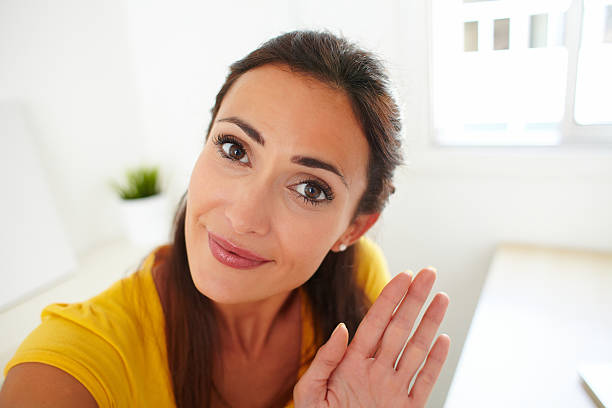 latin lady greeting a person on webcam - webcam stock photos and pictures