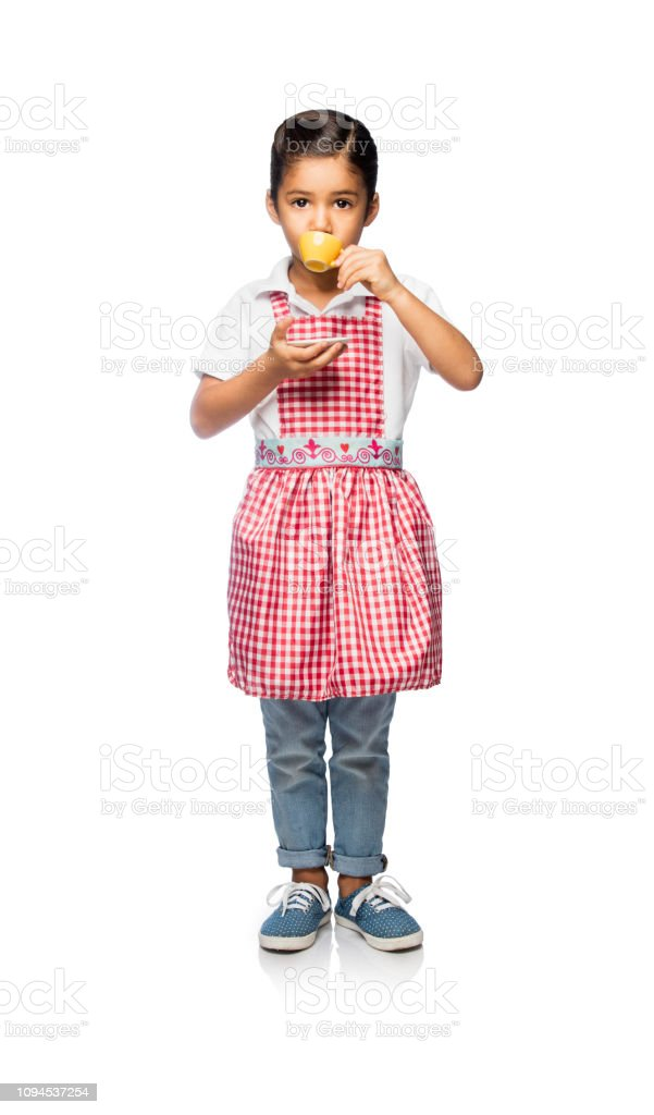 Latin little girl drinking tea and playing stock photo