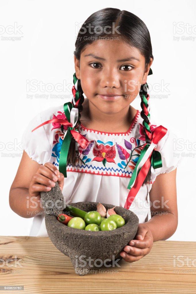 Latin little girl making hot salsa stock photo