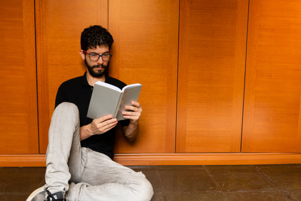 Latin Looking To Distract Himself By Reading Book During Quarantine In His Room Stock Photo Download Image Now Istock