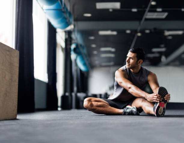 Latin male sitting on the floor of the gym stretching leg muscles stock photo