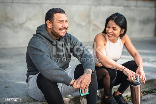 Latin man and woman athlete sitting on the pavement and taking a break