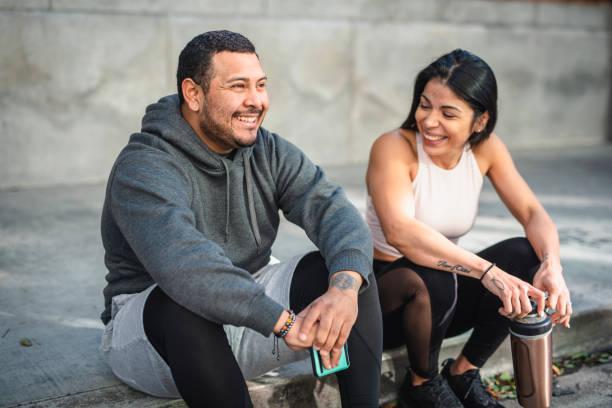Lateinischer Mann und Frau Athleten auf dem Bürgersteig sitzen und eine Pause einlegen – Foto