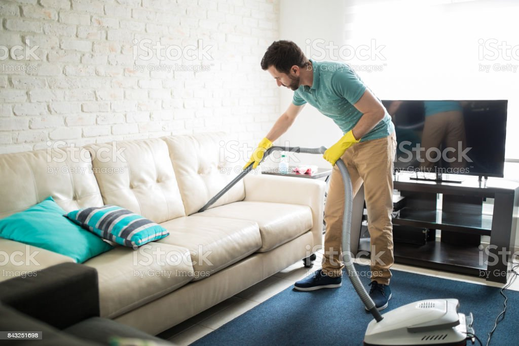 Latin man cleaning the sofa - foto stock
