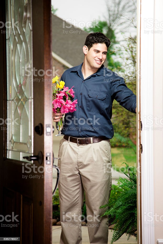 Latin man delivering flowers for Mother's Day or Valentine's. Door. stock photo
