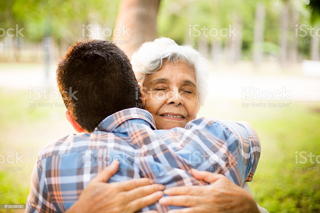 Latin man embracing senior latin woman outdoors - foto de stock