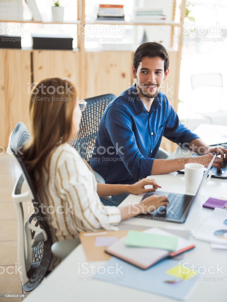 Latin man in the office with coworker stock photo