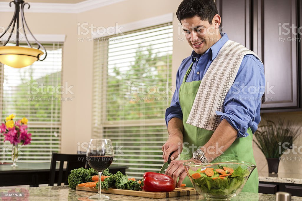 Latin man prepares dinner in home kitchen. Makes healthy salad. royalty-free stock photo