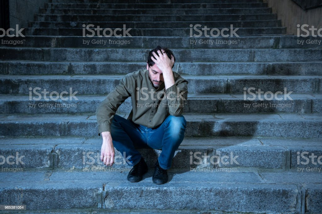 latin man stressed from work sitting on steps outside feeling anxiety in adult cause of depression and problem in living that makes you feel lonely, sad and worried in mental health concept royalty-free stock photo