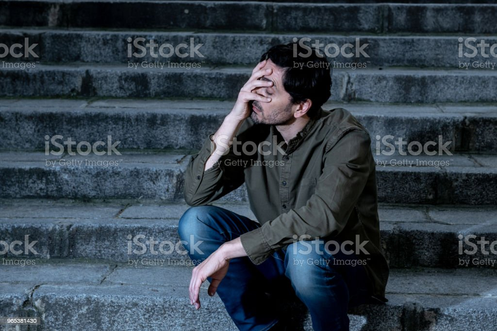 latin man stressed from work sitting on steps outside feeling anxiety in adult cause of depression and problem in living that makes you feel lonely, sad and worried in mental health concept zbiór zdjęć royalty-free