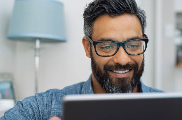 Latin man using digital tablet Relaxed mature man at home using digital tablet. Handsome hispanic man using laptop on sofa. Confident multiethnic guy with spectacles and beard using digital laptop. smirking stock pictures, royalty-free photos & images
