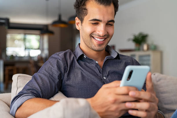 Latin man using smartphone at home stock photo