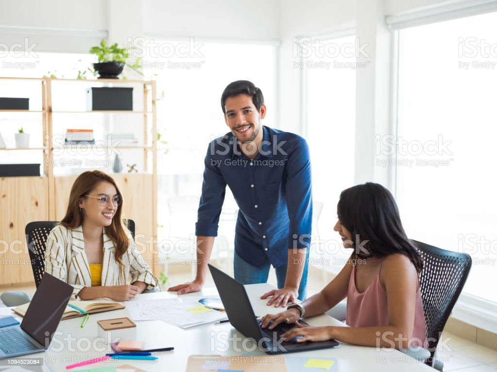 Latin man working with his team stock photo
