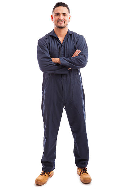 Latin mechanic wearing overalls Full length view of a handsome Latin mechanic wearing overalls and smiling with his arms crossed; bib overalls stock pictures, royalty-free photos & images