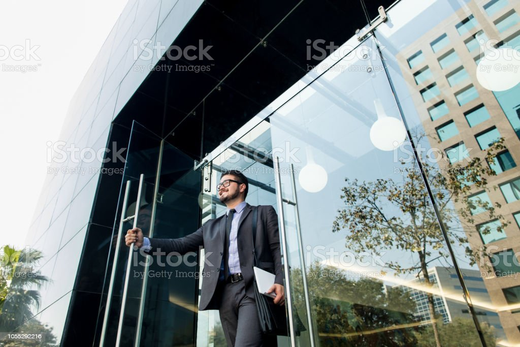 Latin millennial business man walking out of building stock photo