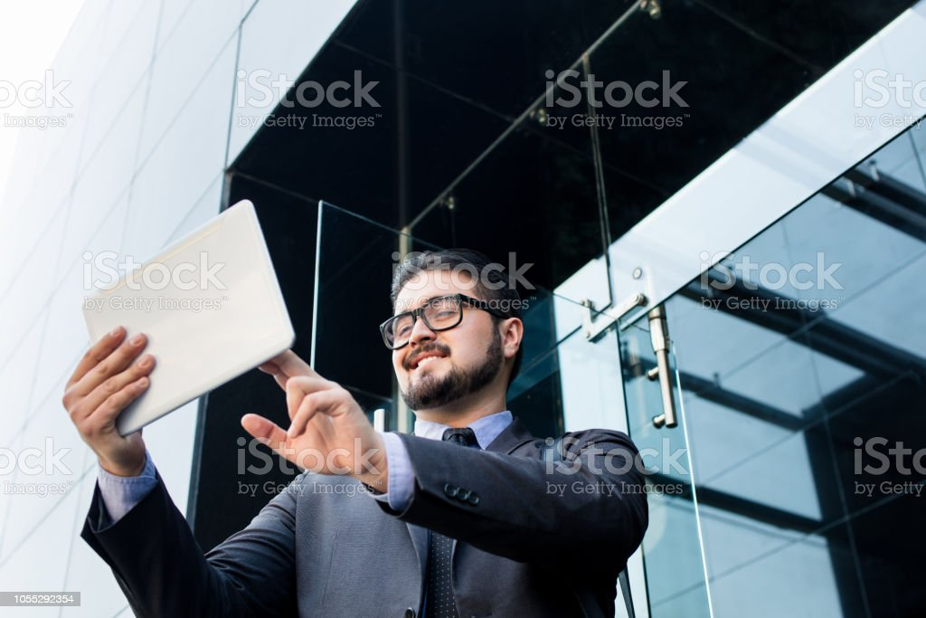 Latin millennial business man with tablet in hand stock photo