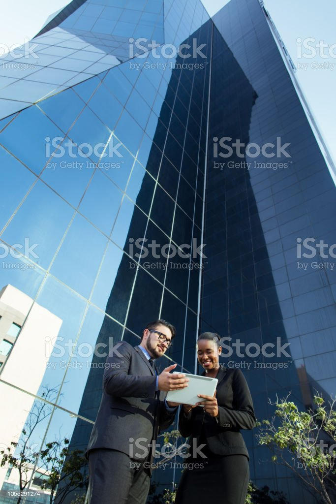 Latin millennial business partners reading from tablet outside stock photo