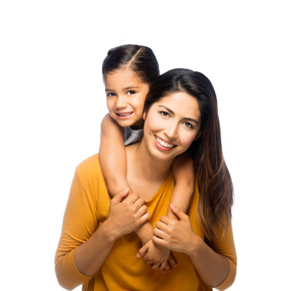 Latin mother and daughter being playful A cheerful mother giving her daughter a piggy back ride on an isolated white background medium shot stock pictures, royalty-free photos & images
