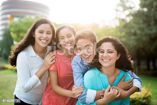istock Latin mother and teenage children smiling at camera 614048730