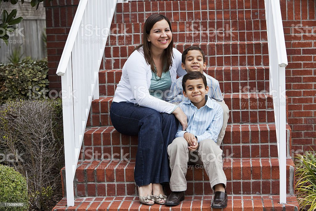 Latin mother and twin boys outside townhouse stock photo