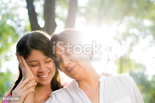 istock Latin mother holding daughter's head and smiling 615495382
