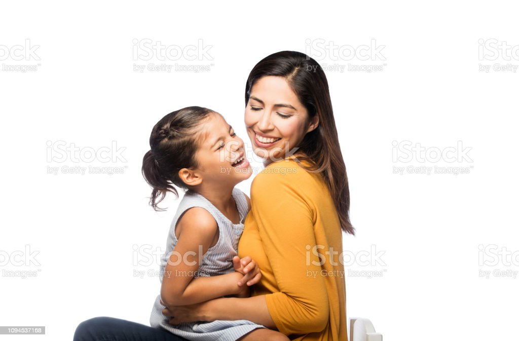 Latin mother tickling her daughter stock photo