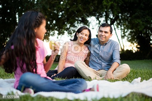 811227514 istock photo Latin parents smiling at daughter with apple 811227328