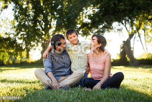 811227514 istock photo Latin parents with one child sitting outdoors 811227514