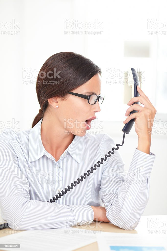 Latin professional employee screaming on the phone royalty-free stock photo