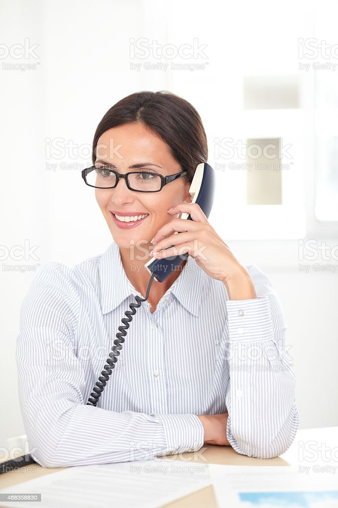 Latin receptionist conversing on the phone royalty-free stock photo