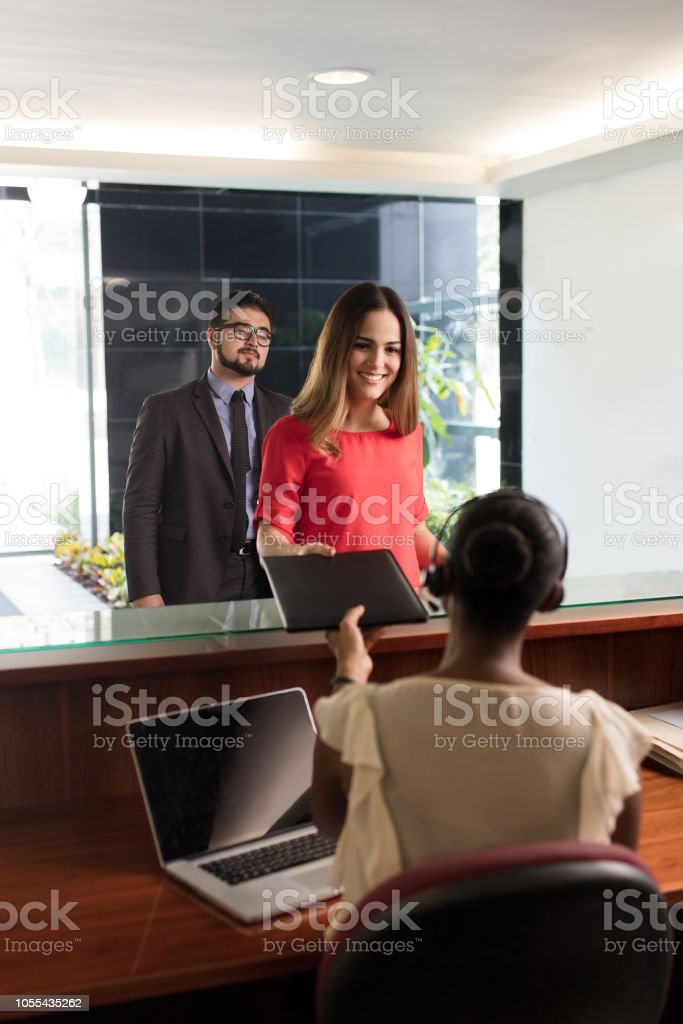 Latin receptionist receiving documents from business women stock photo