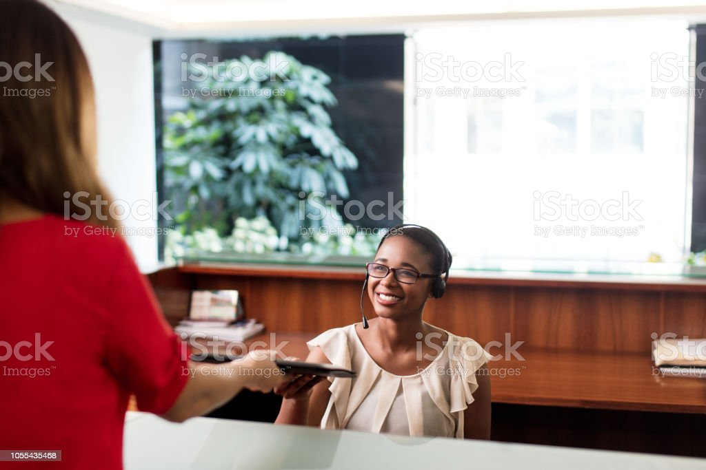 Latin receptionist taking documents from client at the office stock photo