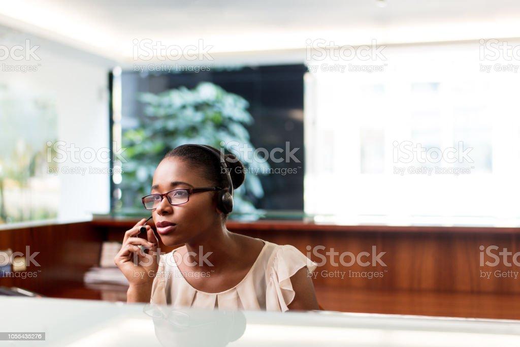 Latin receptionist taking phone call at work stock photo