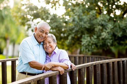 Latin senior couple posing on bridge