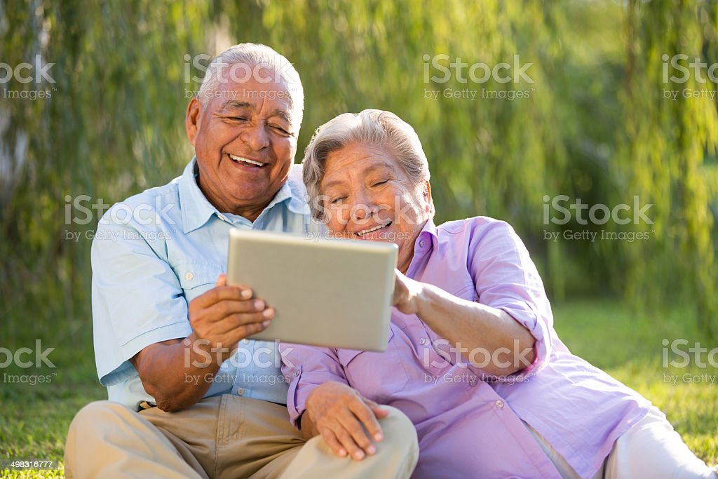 Latin senior couple with a tablet in park stock photo