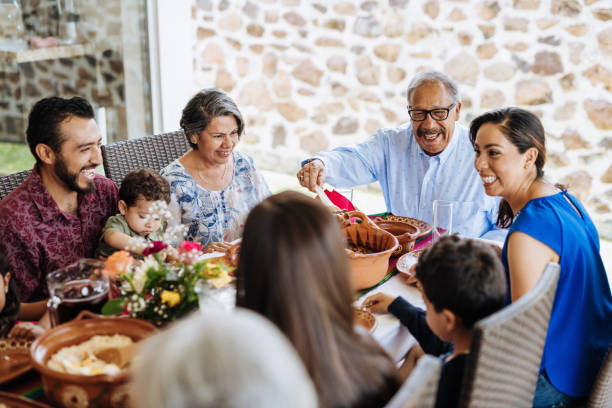 Latin senior man serving the food to his family at dinner table Three generation family at lunch latin american and hispanic ethnicity stock pictures, royalty-free photos & images